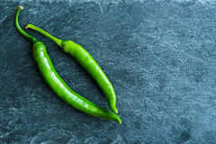 Closeup on green chili peppers on stone substrate Royalty Free Stock Images