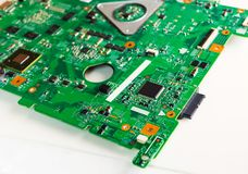 Printed Circuit Board with many electrical components. Closeup of green computer motherboard and wires stock photos