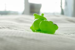 Closeup of a green dinosaur toy on a bed with  white sheets and white bedding, depicting parenting life and playful home with kids royalty free stock image