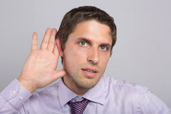 Closeup of a green eyed businessman with hand to ear Stock Photos