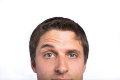 Closeup of a green eyed man raising eyebrow Stock Images