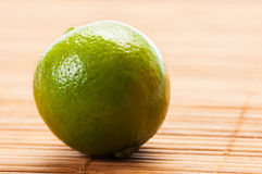 Closeup of a green lime on bamboo table Stock Images