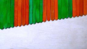 Green Orange Ice Cream Sticks on Wood Background Royalty Free Stock Photo