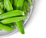 Closeup green peas in pods on white plate top view. Isolated on white background Royalty Free Stock Photos