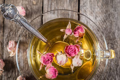 Closeup of green tea cup with dried roses Royalty Free Stock Photos