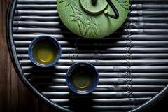 Closeup of green tea with teapot on black bamboo table. Closeup of green tea with teapot on bamboo table Stock Photos
