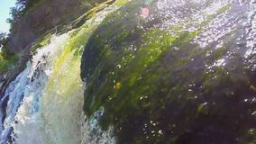 Closeup of green water running over the rocks, waterfall, slowmo. Stock footage stock video footage