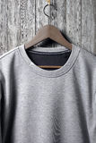 Closeup of grey jumper hanging on wood wall Royalty Free Stock Photo