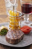 Grilled steak. Closeup of grilled steak with french fries royalty free stock photography