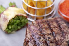 Grilled steak. Closeup of grilled steak with french fries stock photography
