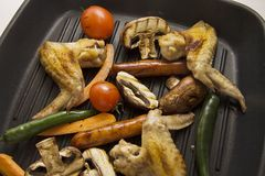 Closeup of grilling  legs and wings with vegetables, horizontal Stock Image