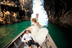 closeup groom blonde bride in fluffy sit on longtail boat nose Royalty Free Stock Photos