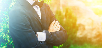 Closeup groom in a blue suit, white shirt and tie butterfly arms crossed against a background of a green bush. Royalty Free Stock Image