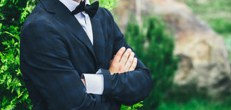 Closeup groom in a blue suit, white shirt and tie butterfly arms crossed against a background of a green bush. Stock Photography