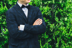 Closeup groom in a blue suit, white shirt and tie butterfly arms crossed against a background of a green bush. Stock Images