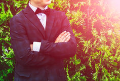 Closeup groom in a blue suit, white shirt and tie butterfly arms crossed against a background of a green bush. Stock Image