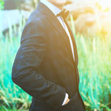 Closeup groom in a blue suit, white shirt and tie butterfly holds hands in pockets on a background of a green bush Royalty Free Stock Photos