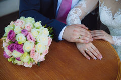 Closeup groom and bride are holding hands at wedding day ang show rings. Concept of love family Royalty Free Stock Photography