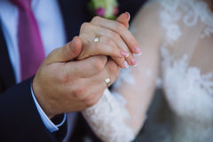 Closeup groom and bride are holding hands at wedding day ang show rings. Concept of love family Royalty Free Stock Photo