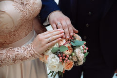 Closeup groom and bride are holding hands at wedding day ang show rings. Concept of love family Stock Photos