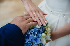 Closeup groom and bride are holding hands at wedding day ang show rings. Concept of love family Stock Photo