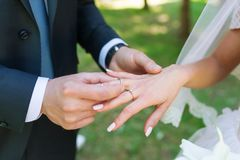 Closeup of the groom placing a wedding ring on the brides hand. royalty free stock photo
