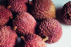 A macro view of pink lychees lying on a white table royalty free stock image