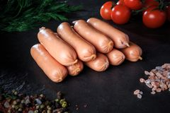 Closeup group of long sausages with rucola and tomatoes. Closeup group of raw long thick sausages with pink salt, spices, rucola and tomatoes cherry on black royalty free stock photo
