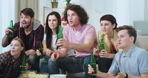 Closeup group of multi ethnic friends celebrating the victory of their best football team in front of TV they watching. The match very excited stock video