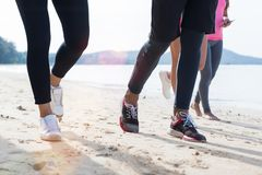 Closeup Of Group Of People Running On Beach Feet Shot Sport Runners Jogging Working Out Team Men And Women Fitness. Training Together On Seaside stock photo