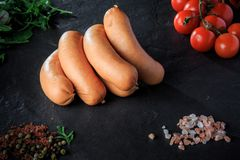 Closeup group of short sausages with rucola and tomatoes. Closeup group of short thick sausages with pink salt, spices, green rucola and tomatoes cherry on black royalty free stock photos