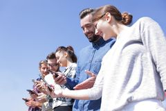 Group of young people with modern gadgets. Closeup of a group of young people with modern gadgets Stock Photo