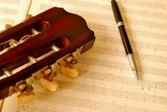 Closeup of guitar with pen on music manuscript. With sepia effect. For concepts like music composition and creativity Royalty Free Stock Photos