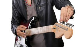 Closeup of guitar tuning. Close up of guitarist checking his instrument's tuning, isolated on white background Royalty Free Stock Photography