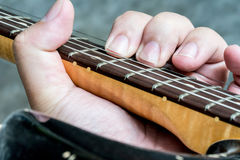 Closeup on guitarist hand playing his vintage guitar Royalty Free Stock Photography