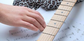 Closeup of a guitarist touching sheet music . on a whit. E background.photo with copy space royalty free stock image