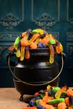 Closeup gummy halloween candy in cauldron. On table Royalty Free Stock Photo