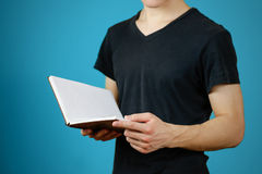 Closeup of guy in black t-shirt holding blank open white book on. Isolated background. Education concept. Mock up Royalty Free Stock Images