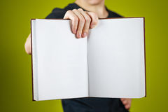 Closeup of guy in black t-shirt holding blank open white book on. Isolated background. Education concept. Mock up Stock Photos