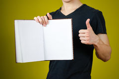 Closeup of guy in black t-shirt holding blank open white book an. D thumb up on isolated background. Education concept. Mock up Royalty Free Stock Photography