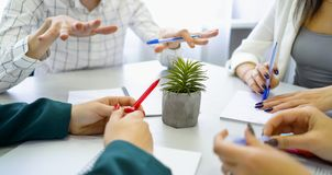 Closeup guy and girls student hands with pens and notebooks on table royalty free stock photos