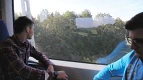 Guy surfs Internet man watches landscape travelling by train. Closeup guy in glasses surfs Internet and man watches landscape through window travelling by train stock footage