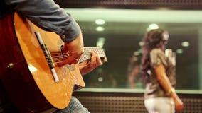 Closeup Guy Plays Guitar Girl Sings på repetitionen i studio arkivfilmer