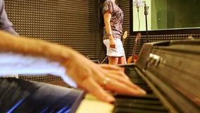 Closeup Guy Plays Piano Girl Sings på repetitionen i studio arkivfilmer