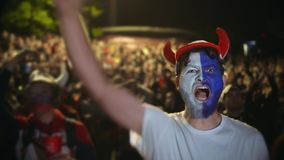 Closeup guy scream furiously, jump friend backdrop crowd to win football soccer stock footage