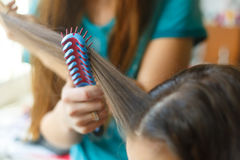 Closeup hairdresser coiffeur makes hairstyle. Blue comb stock photography
