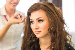 Closeup hairdresser coiffeur makes hairstyle. Closeup hairdresser coiffeur makes hairstyle for young woman stock photos