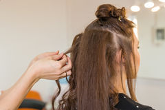 Closeup hairdresser coiffeur makes hairstyle. Closeup hairdresser coiffeur makes hairstyle for young woman stock image