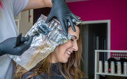 Closeup of hairdresser hands applying hair dye to Stock Photography