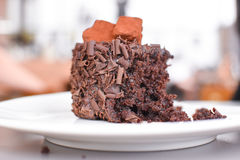 Closeup of half eaten chocolate cake. Side view close up half of tasty chocolate cake on white plate Royalty Free Stock Images